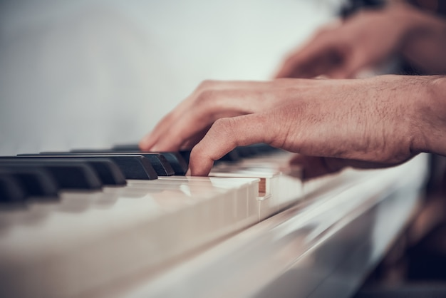 Avvicinamento. man mano che suona il pianoforte. performance musicale. Foto Premium