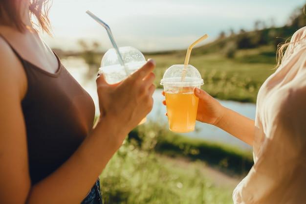 Avvicinamento. ragazze con due bicchieri di plastica con succo d'arancia, con cannuccia, al tramonto, espressione facciale positiva, all'aperto Foto Premium