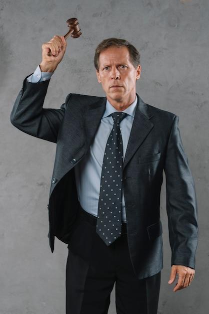 Avvocato maschio maturo che colpisce con il martelletto contro fondo strutturato grigio Foto Gratuite