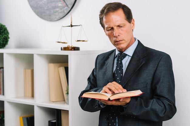 Avvocato maschio maturo che legge libro legale che sta nell'aula di tribunale Foto Gratuite