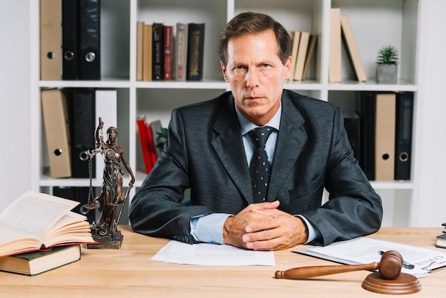 Avvocato maturo sicuro che si siede nell'aula di tribunale Foto Gratuite