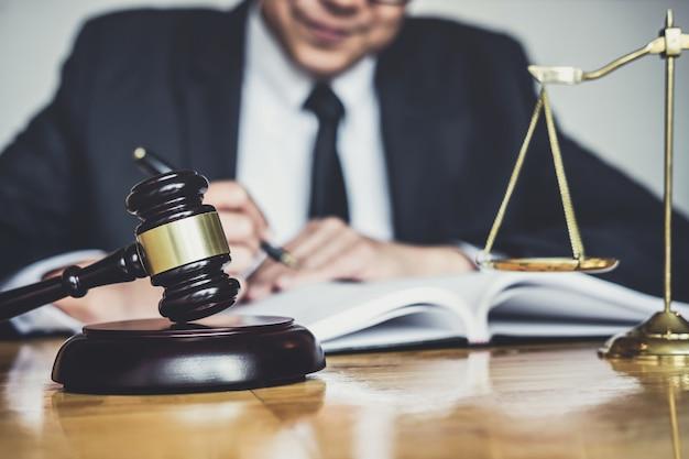 Avvocato o giudice che lavora con documenti contrattuali, libri di giurisprudenza e martelletto di legno sul tavolo in aula Foto Premium