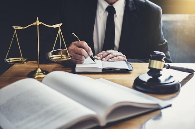 Avvocato o giudice che lavora con documenti contrattuali, libri di giurisprudenza e martelletto di legno sul tavolo Foto Premium
