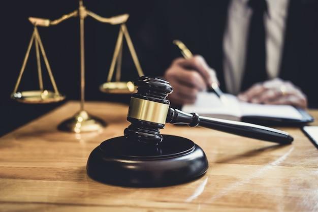 Avvocato o giudice maschio che lavora con le carte del contratto, i libri di legge e il martelletto di legno sul tavolo nell'aula di tribunale Foto Premium