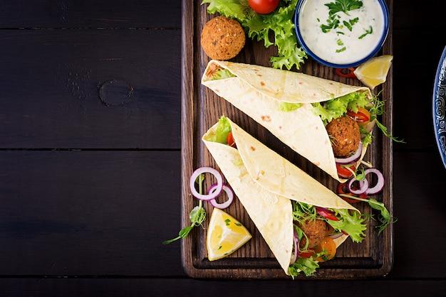 Avvolgere la tortilla con falafel e insalata fresca. tacos vegani. cibo vegetariano sano. vista dall'alto Foto Gratuite
