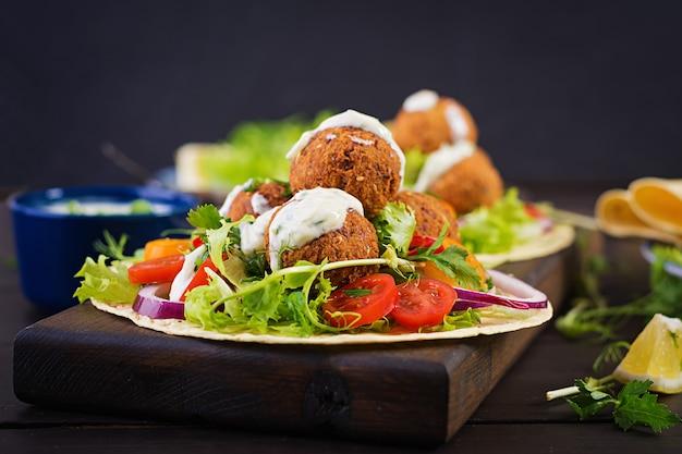 Avvolgere la tortilla con falafel e insalata fresca. tacos vegani. cibo vegetariano sano. Foto Gratuite