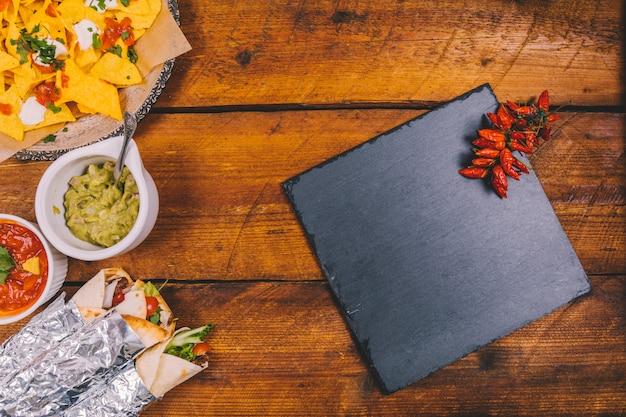 Avvolgi i tacos messicani; gustosi nachos; salsa di salsa; guacamole; ardesia nera e peperoncini rossi sul tavolo di legno marrone Foto Gratuite