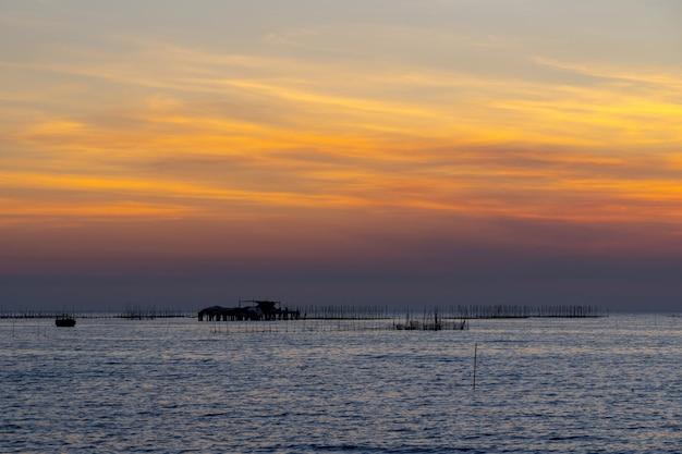 Azienda agricola dell'ostrica nel mare e nella bella priorità bassa di tramonto del cielo Foto Gratuite