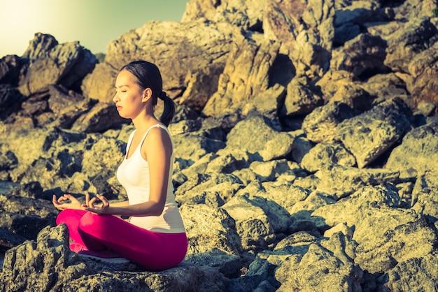 Azione di yoga della giovane donna sulla spiaggia Foto Gratuite