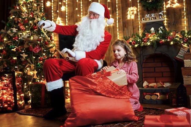 Babbo natale con bambina carina stupita in pigiama regali di imballaggio Foto Premium