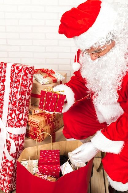 Babbo natale mettendo scatole regalo in grande sacco Foto Gratuite