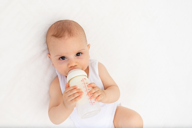 Baby boy 8 mesi sdraiato sul letto nella stanza dei bambini sulla schiena e in possesso di una bottiglia di latte, nutrire il bambino, concetto di pappe Foto Premium