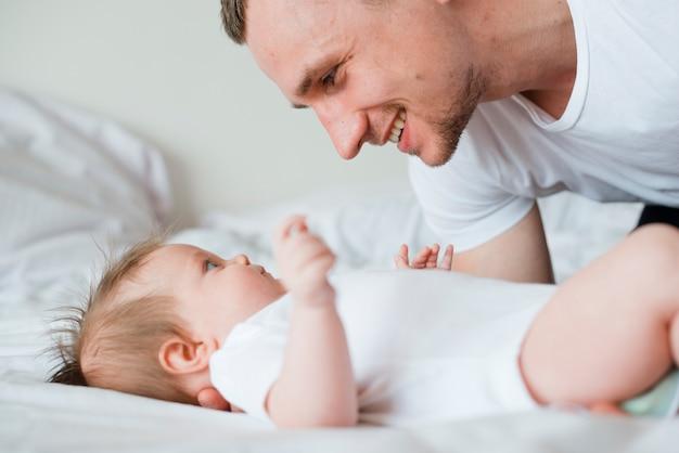 Baby e papà si guardano l'un l'altro a letto Foto Gratuite