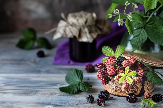 Bacca di blackberry su un ramo con foglie in una scatola di legno intagliato su uno sfondo di legno scuro. Foto Premium