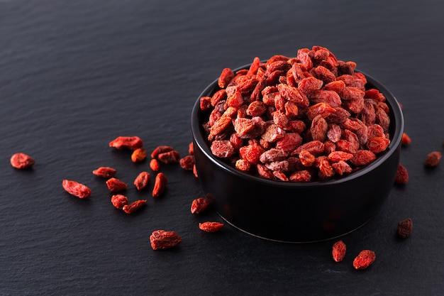 Bacca di goji secca super cibo per il cervello in tazza di ceramica nera su lastra di pietra ardesia Foto Premium
