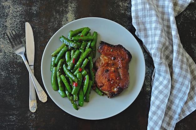 Baccelli di pisello e bistecca di maiale su un piatto. dieta keto. Foto Premium