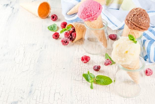 Bacche dolci e dessert estivi, vari gusti di gelato in coni rosa (lampone), vaniglia e cioccolato con menta su cemento leggero Foto Premium