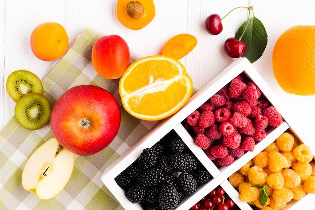Bacche fresche piatte sulla tovaglia con frutta Foto Gratuite