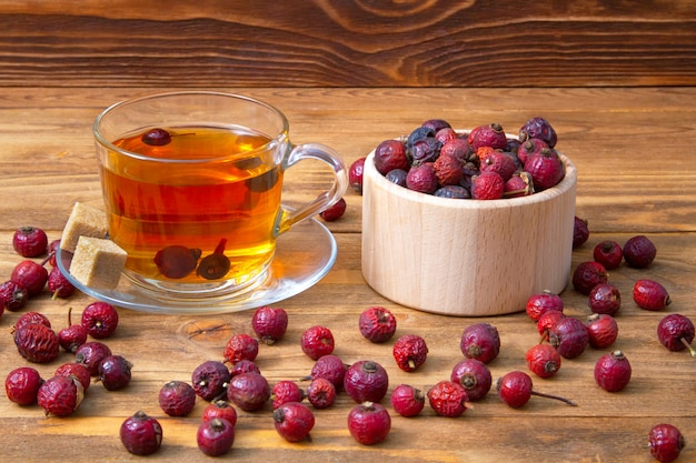 Bacche secche del cinorrodo con una tazza della bevanda aromatica del cinorrodo su legno. bacche curative. Foto Premium