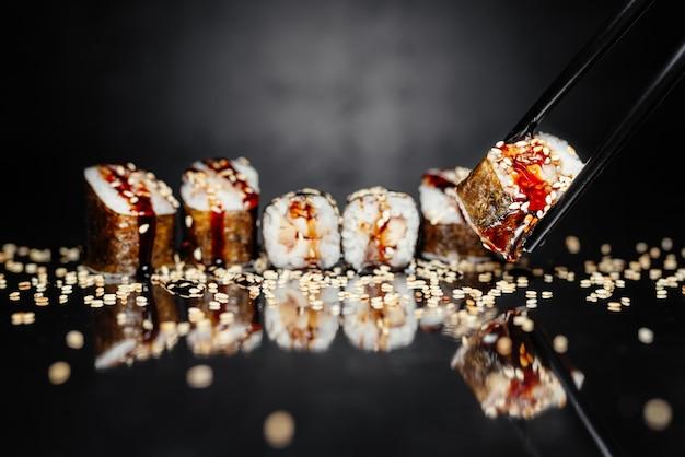 Bacchette che tengono rotolo uguri fatto di nori, riso in salamoia, anguilla / pesce persico unagi Foto Gratuite