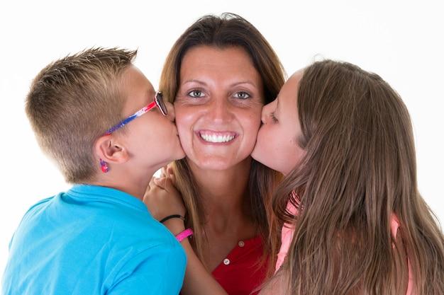 Bacio allegro della madre dall'amore felice della famiglia di concetto dei bambini del ragazzo e della ragazza della figlia del figlio Foto Premium
