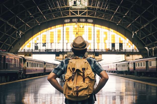 Backpacking asiatico dell'uomo che inizia a viaggiare sulla stazione ferroviaria, viaggio sul concetto di festa. Foto Premium