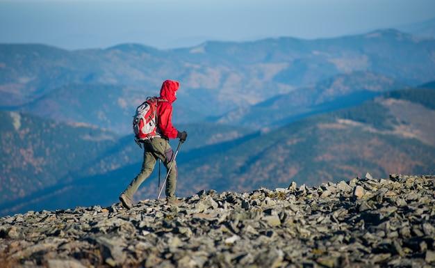 Backpaker maschio che cammina sulla cima rocciosa della montagna Foto Premium