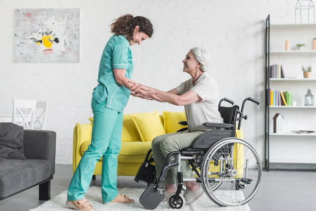 Badante che aiuta paziente femminile senior che si siede sulla sedia a rotelle Foto Gratuite