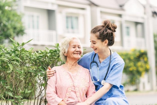 Badante con donna anziana asiatica all'aperto Foto Premium