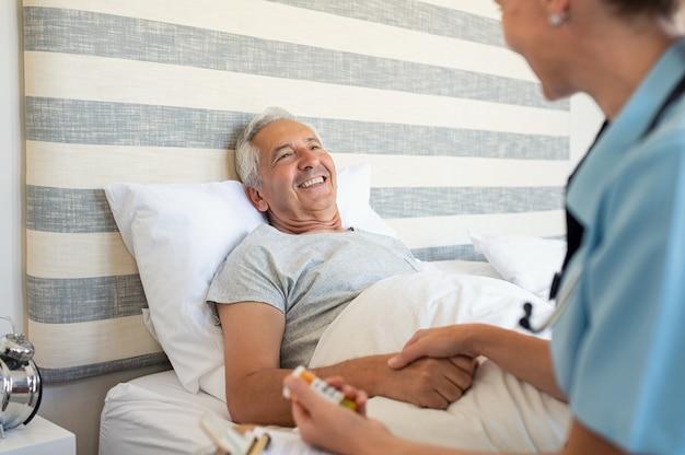 Badante domestico che aiuta un uomo senior Foto Premium