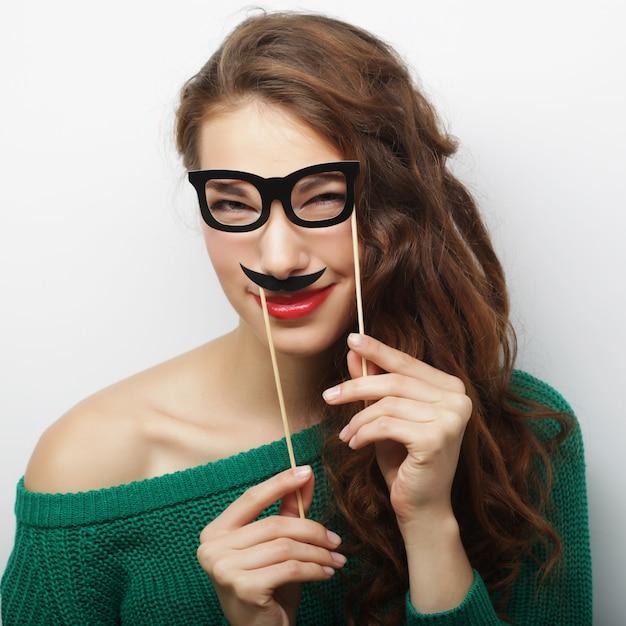 Baffi e vetri allegri allegri della tenuta della giovane donna Foto Premium