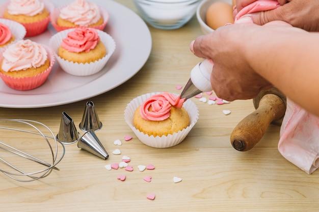 Baker decora i muffin con la crema sulla scrivania di legno Foto Gratuite