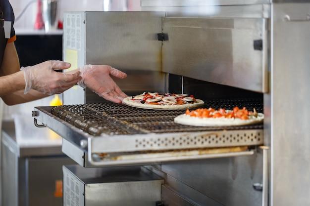 Baker mette la pizza cruda in un forno industriale Foto Premium