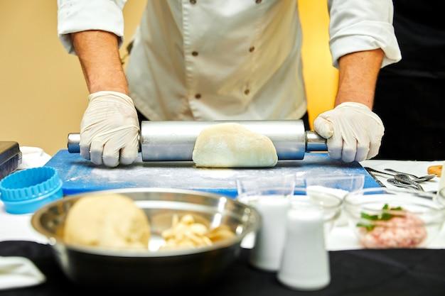 Baker stende la pasta su un tavolo da cucina in legno cosparso di farina Foto Premium