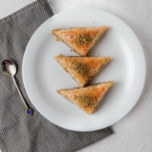 Baklava turca di vista superiore con il cucchiaio e lo straccio in piatto rotondo Foto Gratuite