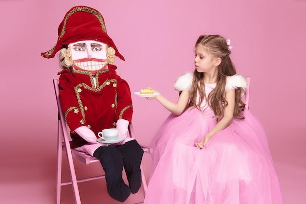 Ballerina di bellezza con schiaccianoci sul rosa Foto Gratuite