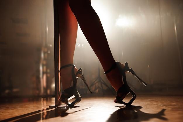 Ballerina di palo, gambe sexy vicino a un pilone. Foto Premium