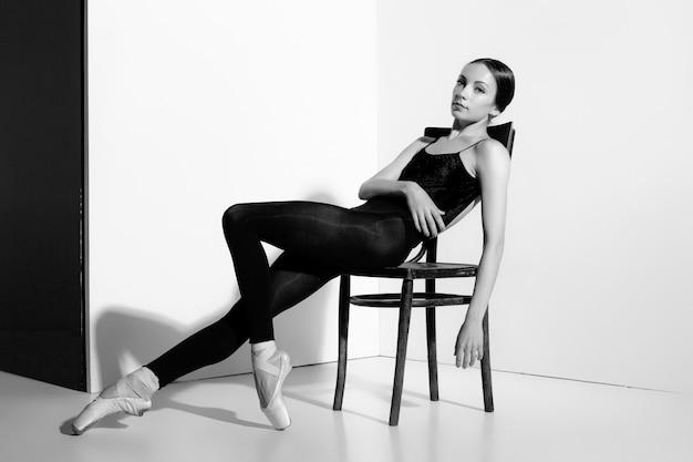 Ballerina in attrezzatura nera che posa su una sedia di legno, fondo dello studio. Foto Gratuite