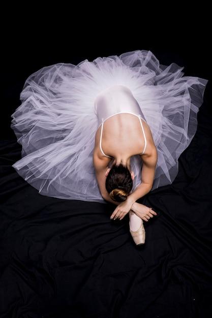 Ballerina seduta su sfondo nero Foto Gratuite