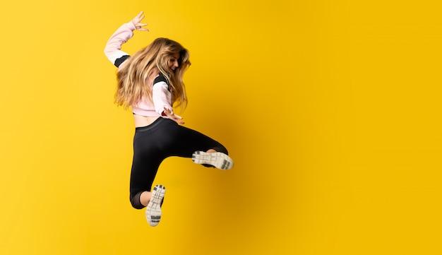 Ballerina urbana che balla sopra fondo giallo isolato e salto Foto Premium