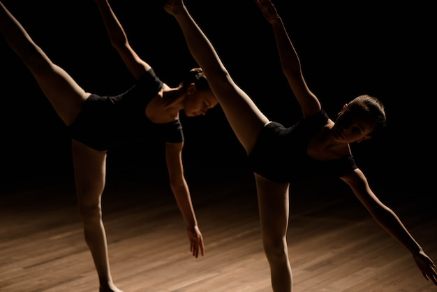 Ballerine flessibili si estendono su una scena scura illuminata Foto Premium