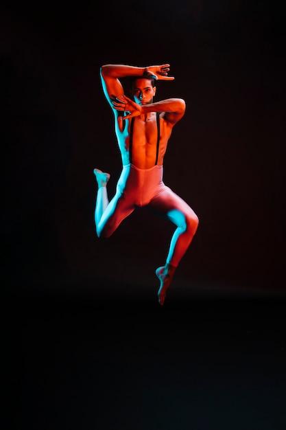 Ballerino di balletto maschio contemporaneo esibendosi sotto i riflettori Foto Gratuite