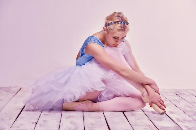 Ballerino di balletto stanco che si siede sul pavimento di legno Foto Gratuite