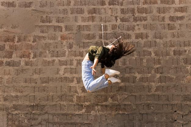 Ballerino femminile flessibile di stile moderno che salta in aria Foto Gratuite