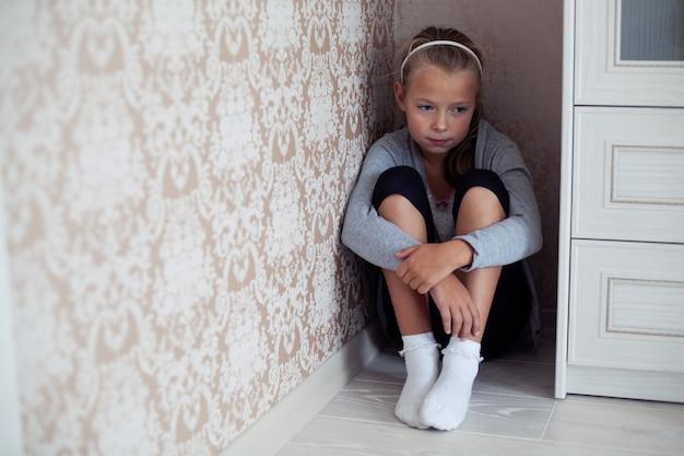 Bambina addolorata seduta nell'angolo della stanza Foto Premium