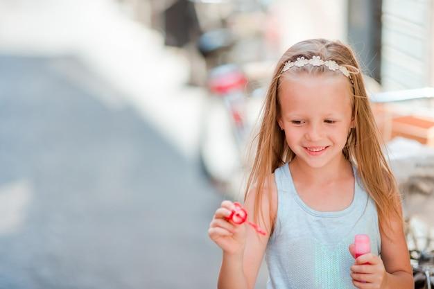 Bambina adorabile all'aperto che soffia le bolle di sapone in città europea. il ritratto del bambino caucasico gode delle vacanze estive in italia Foto Premium