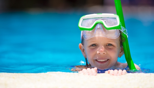Bambina adorabile alla mascherina e agli occhiali di protezione nella piscina Foto Premium