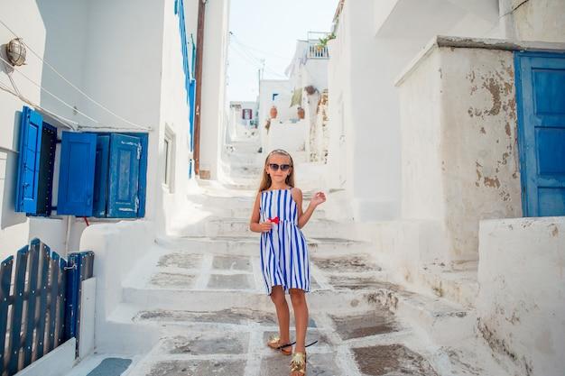 Bambina adorabile alla vecchia via del villaggio tradizionale greco tipico Foto Premium