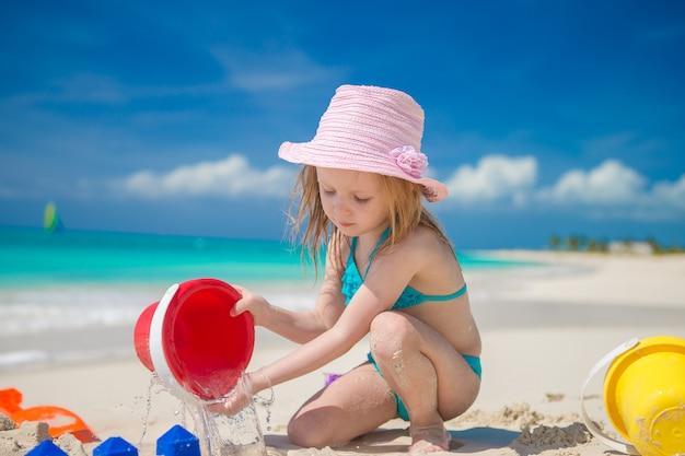 Bambina adorabile che gioca con i giocattoli sulla vacanza della spiaggia Foto Premium