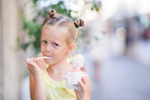 Bambina adorabile che mangia gelato all'aperto all'estate. Foto Premium